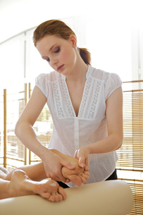 Young woman receiving foot massage from masseuseの写真素材 [FYI03654286]
