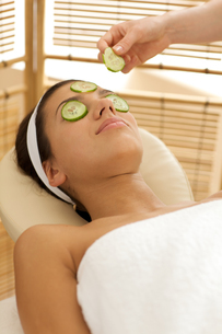 Young woman lying on massage table with cucumber slice being placed over eyeの写真素材 [FYI03654305]