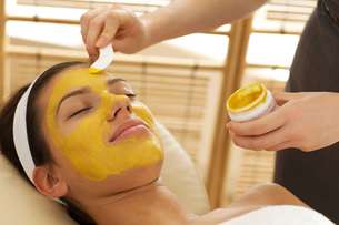 Close-up of young woman having facial mask in beauty parlorの写真素材 [FYI03654309]