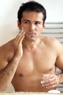Reflection of young man in mirror applying shaving creamの写真素材 [FYI03654383]