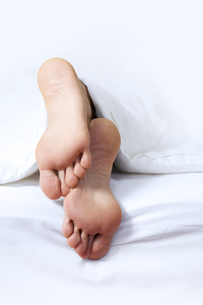 Person's foot in bedの写真素材 [FYI03654395]