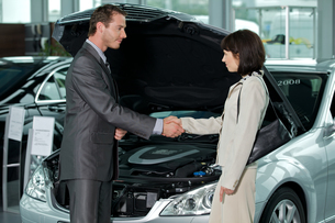 Car salesperson shaking hands with customer at showroomの写真素材 [FYI03654473]