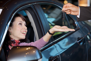 Young woman receiving the car keys from car salesmanの写真素材 [FYI03654488]