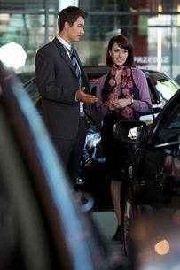 Car salesman explaining car features to customerの写真素材 [FYI03654490]