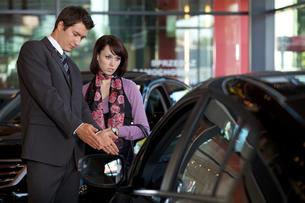 Car salesman explaining car features to customerの写真素材 [FYI03654491]