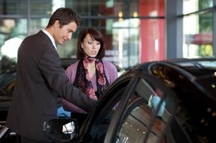Car salesman explaining car features to customerの写真素材 [FYI03654492]