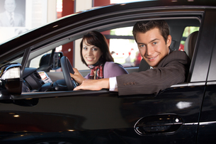 Portrait of young couple sitting in a new car at showroomの写真素材 [FYI03654496]