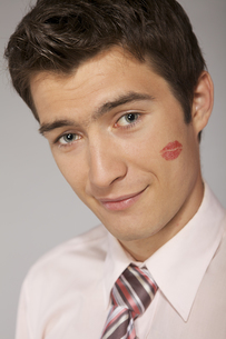 Young caucasian businessman with lipstick kiss mark on his cheekの写真素材 [FYI03654497]