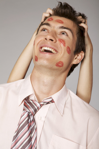 Young caucasian businessman with lipstick kiss mark on his cheekの写真素材 [FYI03654499]