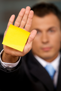 Businessman in office with blank adhesive note stuck to his handの写真素材 [FYI03654534]