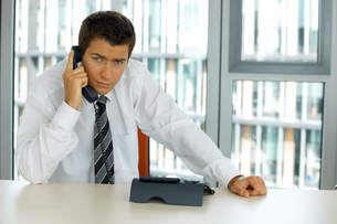 portrait of young confident caucasian businessman talking on phoneの写真素材 [FYI03654594]