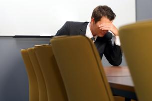 Despaired businessman sitting in officeの写真素材 [FYI03654610]