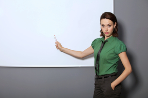 Portrait of businesswoman with hands in pockets pointing at whiteboard in officeの写真素材 [FYI03654624]