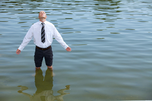 Businessman standing in lake, eyes closedの写真素材 [FYI03654628]