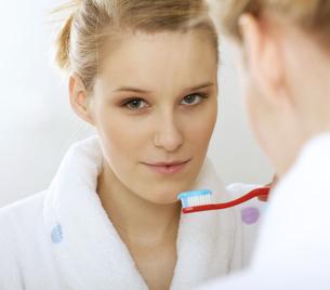 Woman in bathroom brushing teethの写真素材 [FYI03654659]