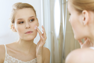 Young woman applying beauty cream, close upの写真素材 [FYI03654668]