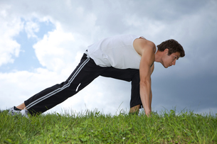 Young man exercising in parkの写真素材 [FYI03654774]