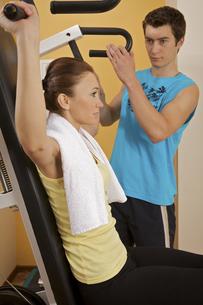 A young woman exercising with a personal trainerの写真素材 [FYI03654861]