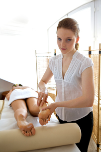 Young woman receiving foot massage from masseuseの写真素材 [FYI03654872]