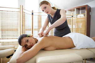 Portrait of young woman receiving massage from masseuseの写真素材 [FYI03654876]