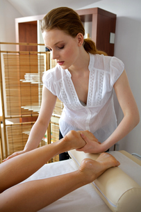 Young woman receiving foot massage from masseuseの写真素材 [FYI03654881]