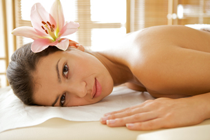 Portrait of young woman relaxing on massage tableの写真素材 [FYI03654892]