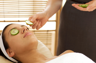 Young woman lying on massage table with cucumber slice being placed over eyeの写真素材 [FYI03654907]