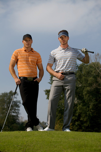 Portrait of young men standing with golf sticks on golf courseの写真素材 [FYI03654913]