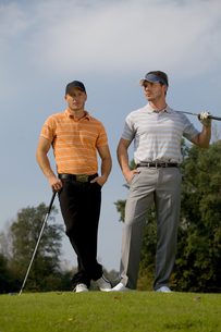 Portrait of young men standing with golf sticks on golf courseの写真素材 [FYI03654918]