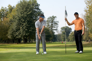 Portrait of young men standing with golf sticks on golf courseの写真素材 [FYI03654919]