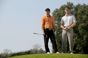 Portrait of young men standing with golf sticks on golf courseの写真素材 [FYI03654921]
