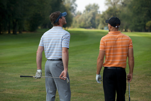 Young men standing in golf course with sticks, rear viewの写真素材 [FYI03654938]
