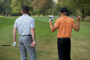 Young men standing in golf course with sticks, rear viewの写真素材 [FYI03654940]