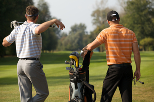 Young men standing in golf course by golf bag full of sticksの写真素材 [FYI03654945]