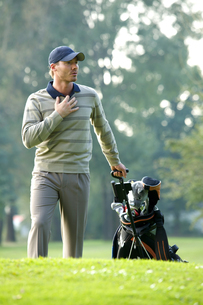 Young man carrying trolley with golf bagの写真素材 [FYI03654970]