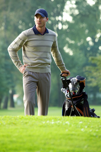 Young man carrying trolley with golf bagの写真素材 [FYI03654973]