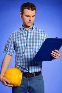 Architect holding hardhat and looking at clipboardの写真素材 [FYI03654976]
