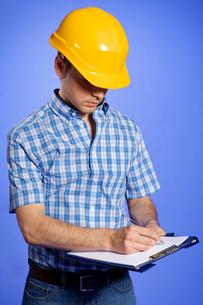 Architect in yellow hardhat writing on clipboardの写真素材 [FYI03654977]