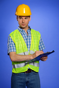 Architect in coveralls and hardhat using clipboardの写真素材 [FYI03654982]