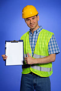 Portrait of architect holding clipboard and showing thumbs up signの写真素材 [FYI03654989]