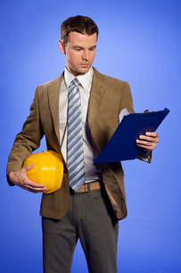 Businessman holding hardhat and looking at clipboardの写真素材 [FYI03654991]