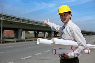 Portrait of architect in hardhat holding blueprint and gesturingの写真素材 [FYI03655004]