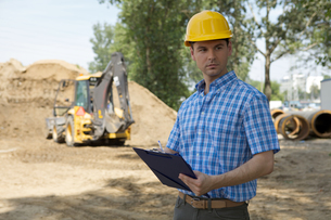 Architect holding clipboard at construction site, bulldozer in backgroundの写真素材 [FYI03655007]