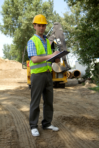 Portrait of architect using clipboard at construction siteの写真素材 [FYI03655013]