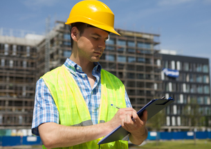Architect writing on clipboard at construction siteの写真素材 [FYI03655016]