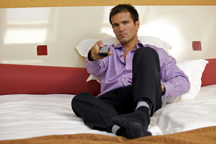 Portrait of man on bed using remote controlの写真素材 [FYI03655061]
