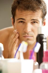 Reflection of young man in mirror applying shaving creamの写真素材 [FYI03655090]