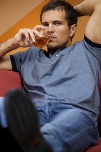 Portrait of young man drinking whisky in hotel roomの写真素材 [FYI03655107]