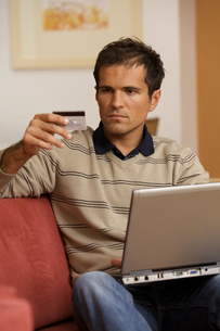 Young man holding credit card and using laptopの写真素材 [FYI03655128]