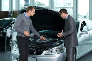 Car salesperson explaining about car's engine to customerの写真素材 [FYI03655225]